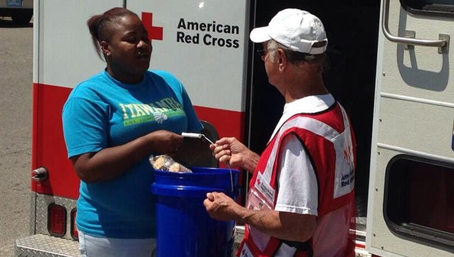 A Tupelo, Miss. resident receives supplies from a Red Cross volunteer