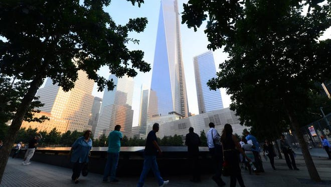 Friends and family members gather at the 9/11 Memorial during ceremonies marking the 12th anniversary of the 9/11 attacks on the World Trade Center in New York, Sept. 11, 2013. (AP Photo/Alejandra Villa, Pool)