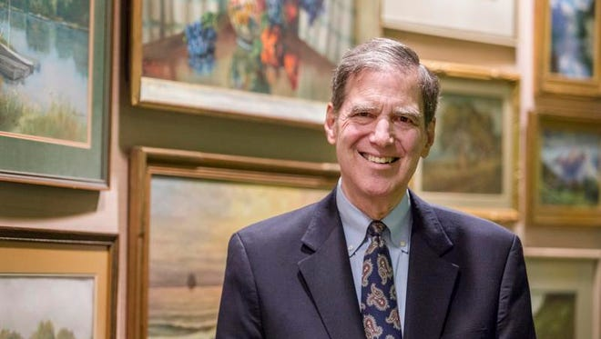 Dick Poole poses for a portrait in front of several pieces of his art collection in his gallery at the Park Plaza in Wilmington. Poole is donating numerous pieces to an art auction benefiting Habitat for Humanity.
