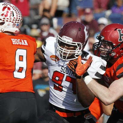 North squad offensive tackle Cole Toner of Harvard (79) fails at holding back South squad defensive end Noah Spence of Eastern Kentucky (97) when he sacks North squad quarterback Kevin Hogan of Stanford (8) during Saturday's Senior Bowl in Mobile, Alabama.