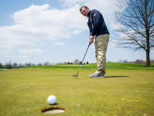 Golf pro Matt Smith putts at the Players Club in Yorktown.