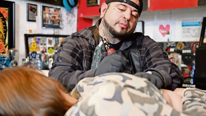 Tattoo artist Eric Catalano performs an areola tattoo procedure on Terri Battista's breasts at Eternal Ink Tattoo Studio in Hecker, Ill. After a double mastectomy following cancer in 2013, Battista had reconstructive surgery but held off on areola tattoos because of the cost. Then she heard about Catalano's shop, where breast cancer survivors could get the procedure done for free.