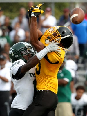 Detroit King's Ambry Thomas, right, lets a pass get out of his reach as Detroit Cass Tech's Alexander Donnell defends him Sept. 26, 2015.