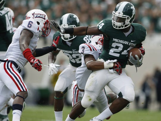 Michigan State's Le'Veon Bell, right, rushes against