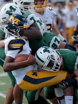 Moeller's Miles McBride (14) is wrapped up by Mason's Alex King during their football game, Sunday, Sept. 11, 2016.