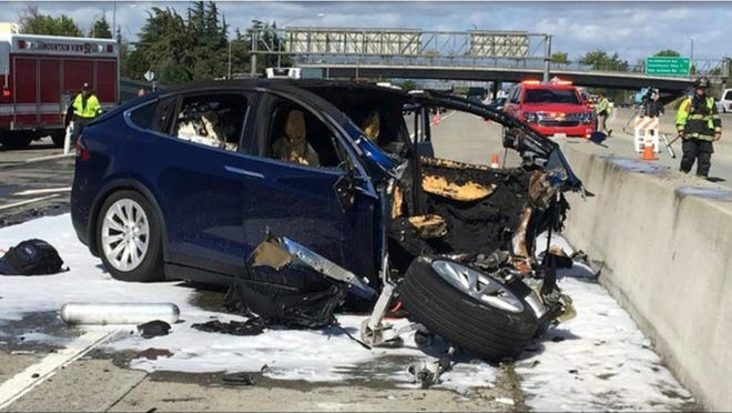 In this March 23, 2018 file photo provided by KTVU, emergency personnel work a the scene where a Tesla electric SUV crashed into a barrier on U.S. Highway 101 in Mountain View, Calif.