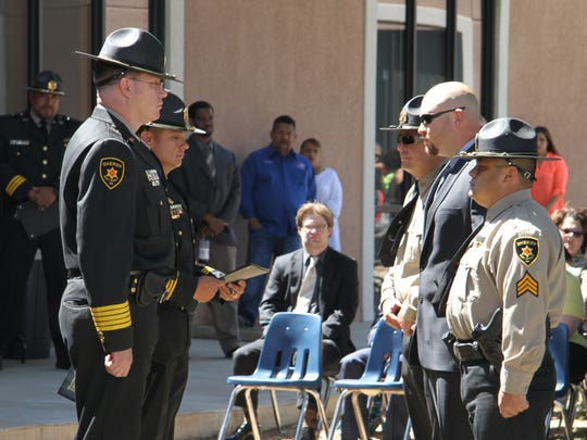 Eddy County Sheriff Scot London, left, honors Sgt. Miguel Garcia, Sgt. Lenin Leos and Sgt. Michael Bird at the Law Enforcement Memorial Wednesday.