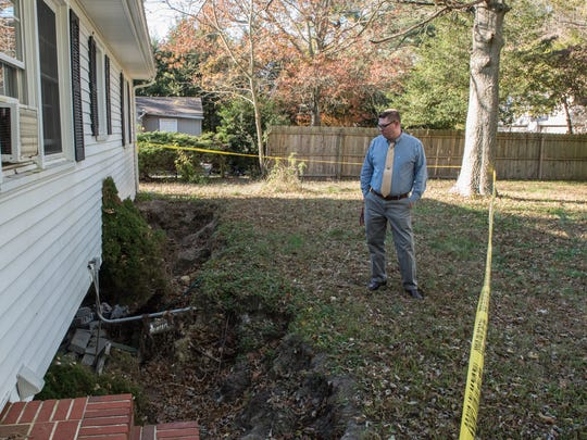 Grady McGrew, of Salisbury, observes the damaged foundation