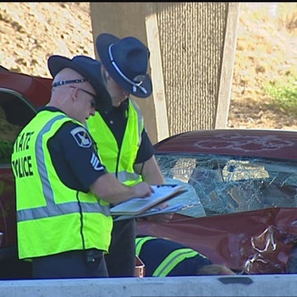 Idaho State Police troopers investigate a car crash.