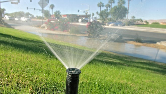 A sprinkler at a business on Dinah Shore Dr. waters a strip of grass, wetting the sidewalk.