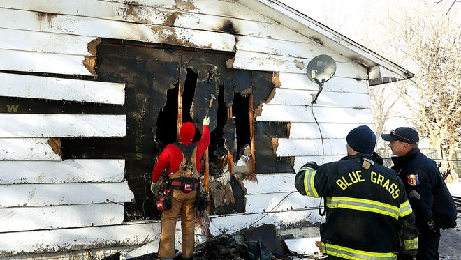Blue Grass Fire Chief Brian Seamer and Blue Grass Police Sgt. Garrett Jahns watch a home being secured on East Salem Street where four people died in a fire Monday Dec. 25, 2017. Jahns said Tuesday that he couldn't release any of the victims' names or ages yet but that the four were related.