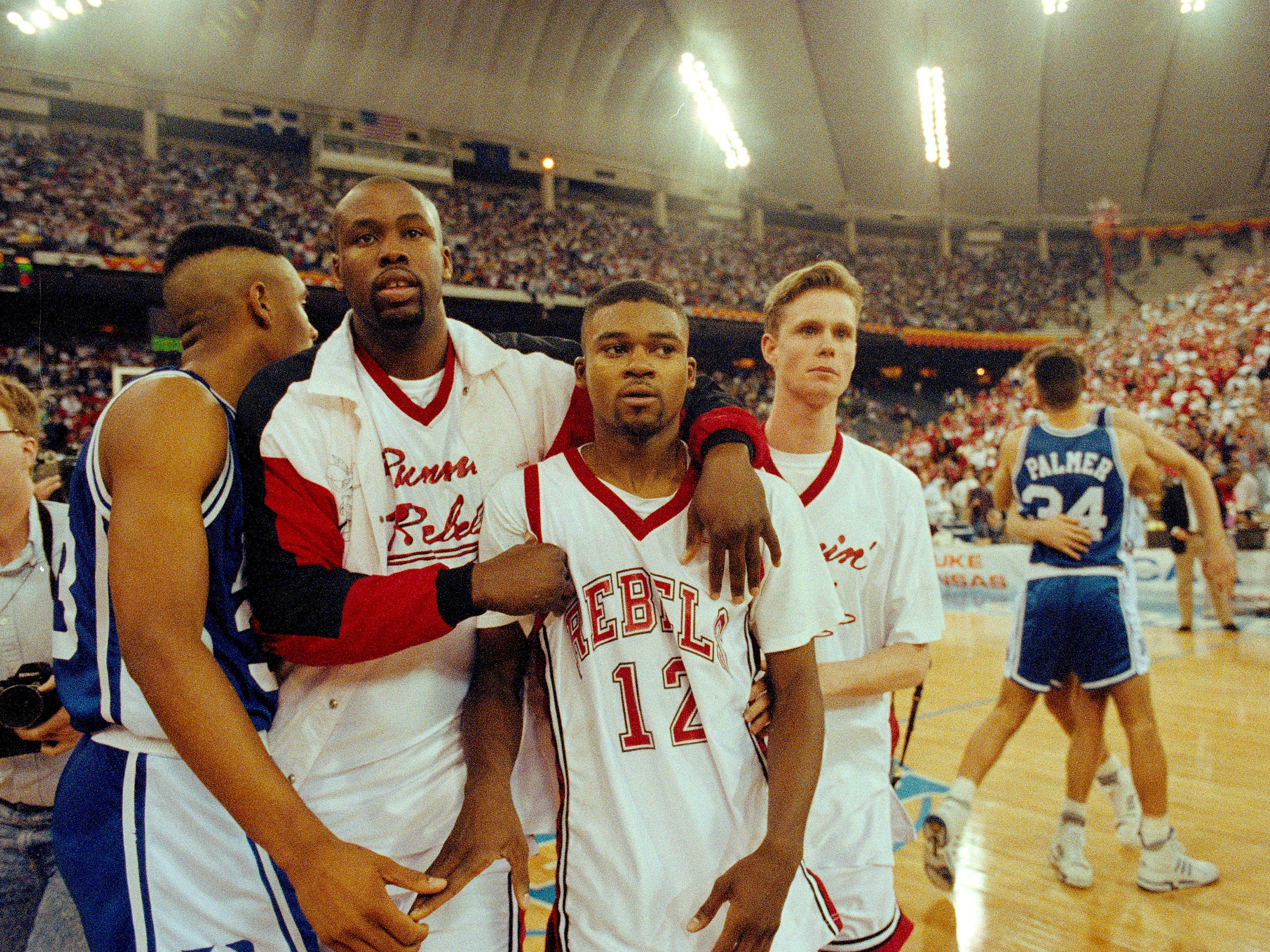 UNLV's Anderson Hunt (12) and unidentified teammates leave the floor after losing to Duke in the NCAA national semi-final game in Indianapolis, March 30, 1991. Duke defeated UNLV by a score of 79-77. (AP Photo/Al Behrman)
