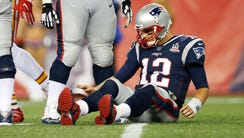 New England Patriots quarterback Tom Brady (12) lies