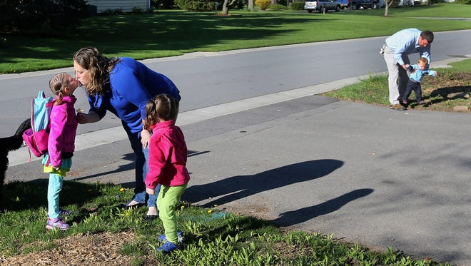 Maggie Walker gives her daughter Abby, 5, a kiss before she gets on the school bus.  Going to school is often a family affair with sister Hadley, 3, dad David and brother Henry, 1, helping out on many mornings. The Walkers moved to Webster in part because they liked the school district.