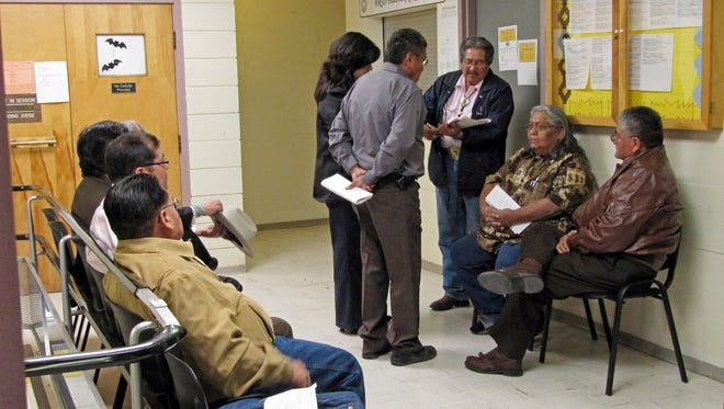 Navajo lawmakers look over criminal complaints filed against them in the lobby of the Window Rock, Ariz., district court on Oct. 21, 2010. More than three-fourths of the lawmakers have been charged in an investigation into the use of slush funds. A long-running saga stemming from allegations that Navajo tribal officials schemed to give money to family members is drawing to a close.