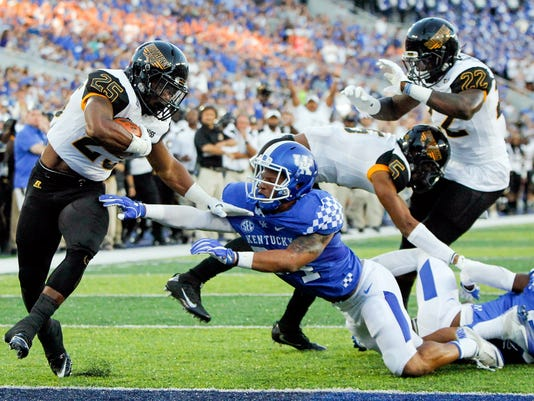 FILE - In this Sept. 3, 2016, file photo, Southern Mississippi running back Ito Smith scores a touchdown after slipping past Kentucky linebacker Jordan Jones in the first half of an NCAA college football game, in Lexington, Ky. Southern Miss rallied for a stunning 44-35 win over Kentucky last year in Lexington. Now the Golden Eagles get a chance to make it two in a row _ and this time the game's at home in Roberts Stadium. (AP Photo/David Stephenson, File)