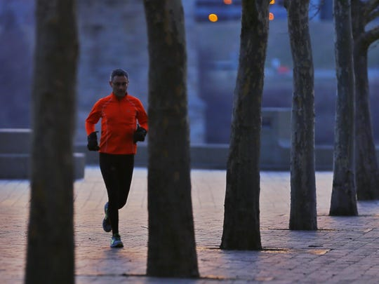 Mark Smith of Munich, Germany, who is in town for business, runs through Sawyer Point just before sunrise.