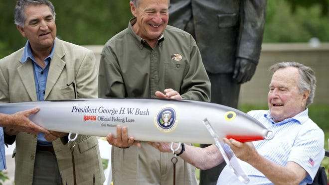 In this April 14, 2016 photo, Bass Pro Shops founder Johnny Morris, center, joins Pedro Sors, president of the fishing association of the Mexican state of Tamaulipas, as they present former president George H.W. Bush with a giant-sized fishing lure at the Bush Library in College Station, Texas. (Dave McDermand/College Station Eagle via AP) MANDATORY CREDIT