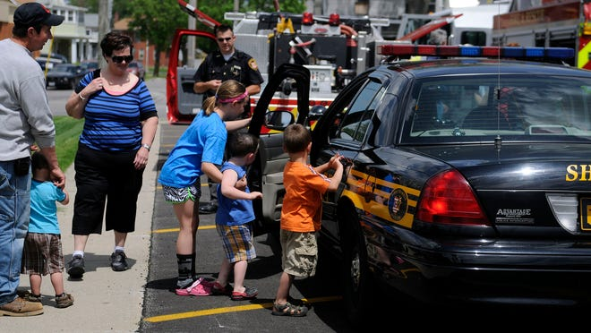 Children check out the inside of Sandusky County Sheriff's Deputy Kenny Arp's cruiser Saturday during the seventh annual Things That Go Show fundraiser at Noah's Ark Pre-School.