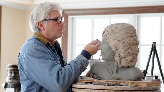 Andy Sacksteder works on a commissioned piece in his new studio space on the Mon Ami Winery grounds on Thursday.