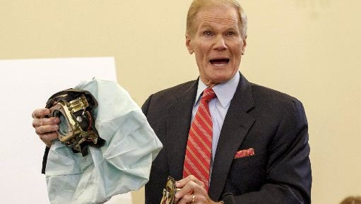 Senate Commerce Committee member Sen. Bill Nelson, D-Fla. displays the parts and function of a defective airbag made by Takata of Japan that has been linked to multiple deaths and injuries in cars driven in the U.S., Thursday, Nov. 20, 2014, during the committee's hearing on Capitol Hill in Washington.