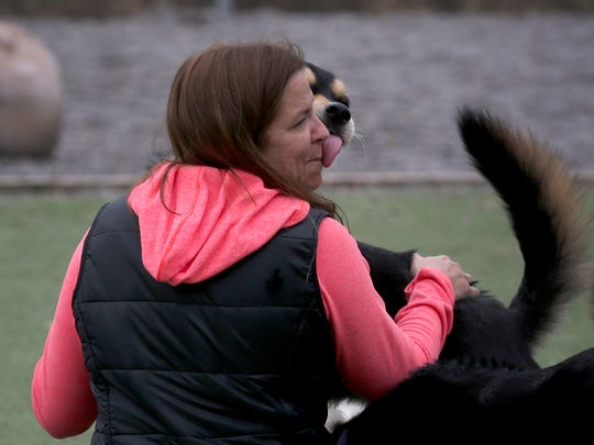 Renee Braddon get a kiss from Tuke, one of her long term clients at her pet hotel, Finger Lakes Pet Resort.