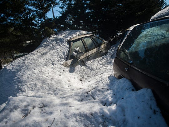 Snow-covered vehicles lie in the lot of the mobile