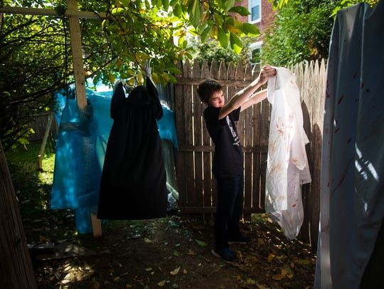 Jacob Ohrum assesses a faux bloody sheet before hanging