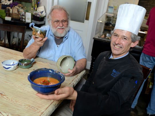 Chef Gus Silivos and the late Bill Clover check out a couple handmade ceramic bowls that were up for grabs at a previous Pick A Bowl Fill A Bowl fundraiser for Manna.