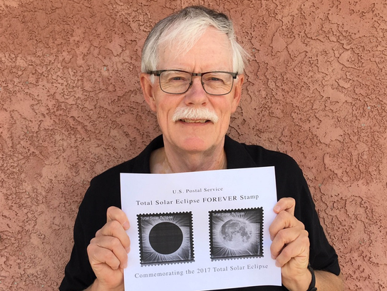 Fred Espenak poses with the designs of the new eclipse