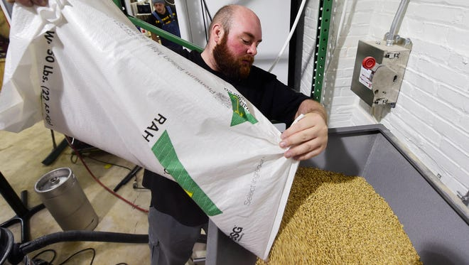 Jared Barnes, head brewer and co-owner of Collusion Tap Works, pours grains into a grain mill as he begins the brewing process on a batch of beer he's calling Bad Trip at the brewery in York Wednesday, September 28, 2016.