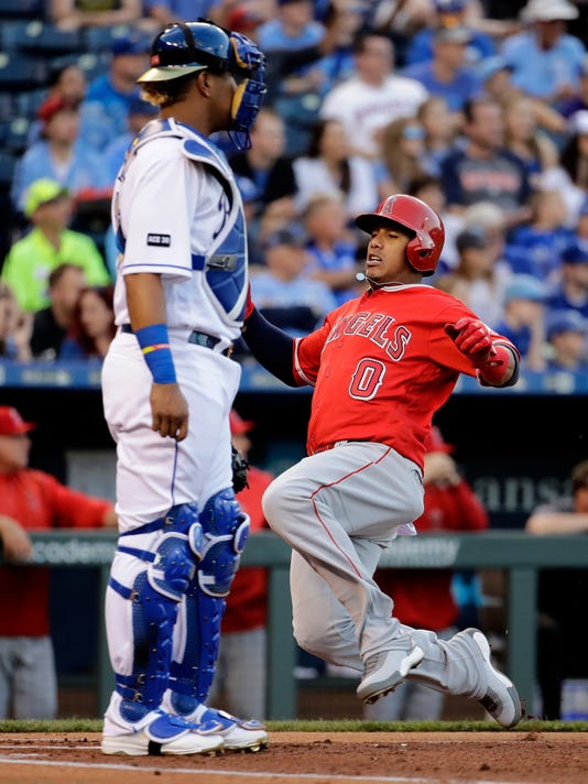 Los Angeles Angels' Yunel Escobar (0) slides home past Kansas City Royals catcher Salvador Perez to score on a single by Mike Trout during the first inning of a baseball game Friday, April 14, 2017, in Kansas City, Mo. (AP Photo/Charlie Riedel)