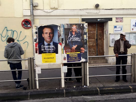 People wait outside a school where election posters