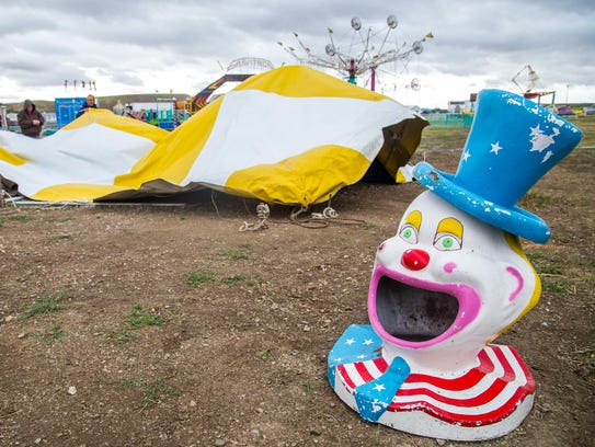 Employees of Funtime Carnivals secure a tent blown