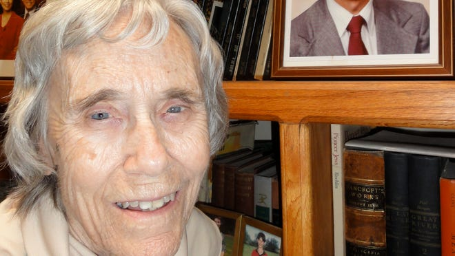 """Martha Ortiz with photo of her late husband Dr. Augusto """"Gus"""" Ortiz"""
