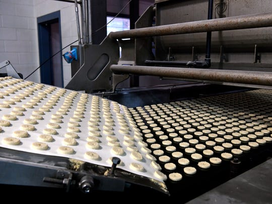 Macaroon cookies roll down down a conveyor on their way to a football field-length oven Feb. 9 at AbiMar Foods. Members of Team Workforce toured three different large Abilene employers to learn more about those companies' workforce needs.