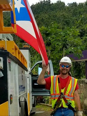 Milford resident Dave Elgin spent 40 days in Puerto Rico to help restore power following the devastation of Hurricane Maria. He is pictured with a Puerto Rico flag that his wife, Kathy, gave him to hang on his DTE truck.