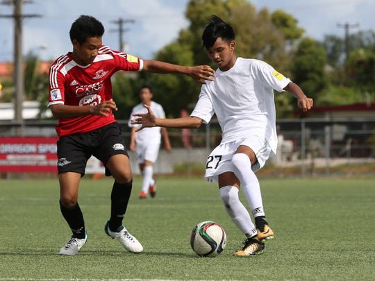 Tigers' John Rafael Garcia controls the ball facing defensive pressure from Wings' Sho Meyar during an opening week U15 division match of the Aloha Maid Minetgot Cup Elite Youth League at the Guam Football Association National Training Center. Wings won 16-1.