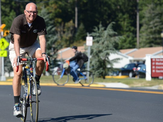 Mike Vizard, owner of Cheers!,  rides his bicycle  down Dogwood Drive in Salisbury on his way to work.