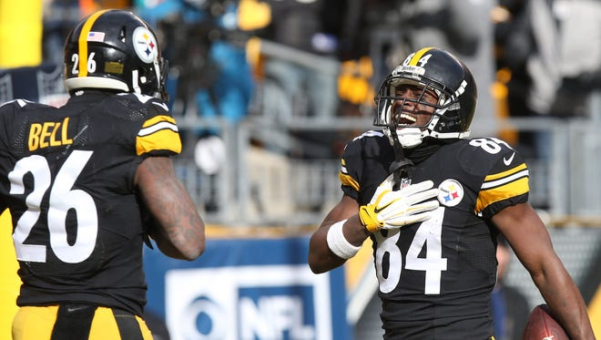 Pittsburgh Steelers wide receiver Antonio Brown (84) celebrates with running back Le'Veon Bell (26) after scoring a touchdown against the Miami Dolphins during the first half in the AFC Wild Card playoff football game at Heinz Field.