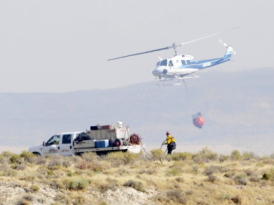 A helicopter flies past a ground crew fighting a wildfire on Aug. 14 scorching grassland that ranchers need to feed cattle and which is also primary habitat for sage grouse, near the Reynolds Creek area in the Owyhee Mountains of Idaho.