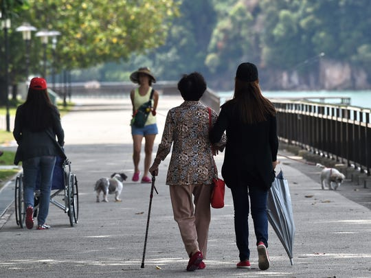 A care-taker walks with an older woman in a park in