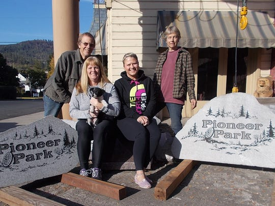 Stayton city employees Michelle Ash, front left, and Kelli Stevens, pose with before the Pioneer Park stone signs before they were transported to Stayton.