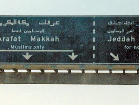 """Christian Bypass"" by Saicome accompanies a Wikipedia page on ""Freedom of religion in Saudi Arabia."" The Wikipedia post says the photo shows a sign on the road to Mecca. https://commons.wikimedia.org/wiki/File:Christian_Bypass.jpg#/media/File:Christian_Bypass.jpg"