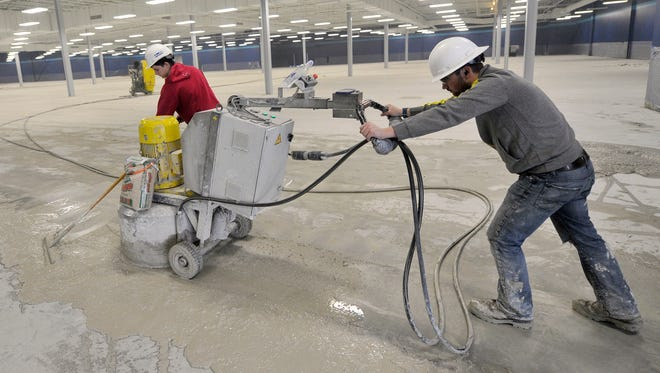 The crew with USA Floor Tech removes the glue from the floor before polishing the concrete in the old Macy's building in West Manchester Township. The home decor retailer, At Home, is slated to open in the space on May 5.