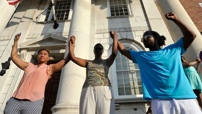 From left: Jada Richardson, Stephanie Seaton and Jamiel Alexander joined hands in front of the York City police station on Friday, July 8, 2016.