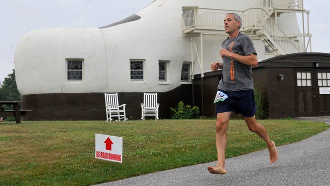 "Hmm. A barefoot runner passing the structure built to promote the sale of shoes. But barefoot with good reason. According to the York Daily Record:  Frank Divonzo of Elizabethtown, runs without footwear while rounding the Haines Shoe House in Hallam during the Shoe House 5-miler. After multiple lower leg injuries, Divonzo said he did research and found that some runners have found success in tackling races without footwear. Although he prefers to scout out a course before a race to check out the terrain, when that's not possible, it leads to stepping in a variety of things. ""I've run through some horse dung."" said Divonzo, who has been running barefoot for the past two years. And when asked if he stops to clean it off, the runner answered, ""It depends on how I'm feeling at that moment. If I need something cool and refreshing on my feet, I keep on trucking."""