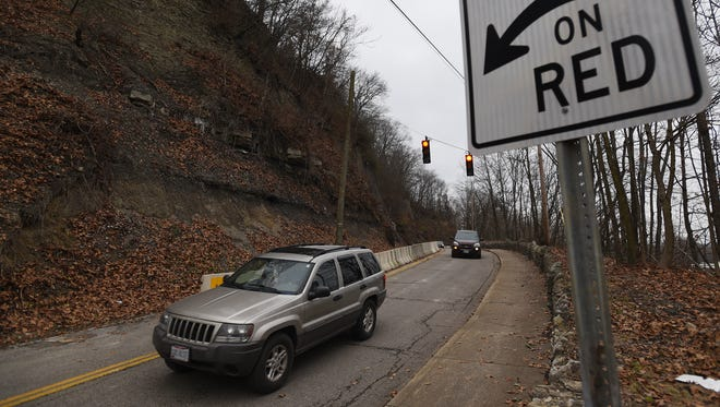 Vehicles traverse Muskingum Avenue, also known as Dug Road, on a section of road that reopened on Monday after being closed for almost a year because of the fear of rock slides. One lane of the road is open and vehicle traffic is guided by lights.