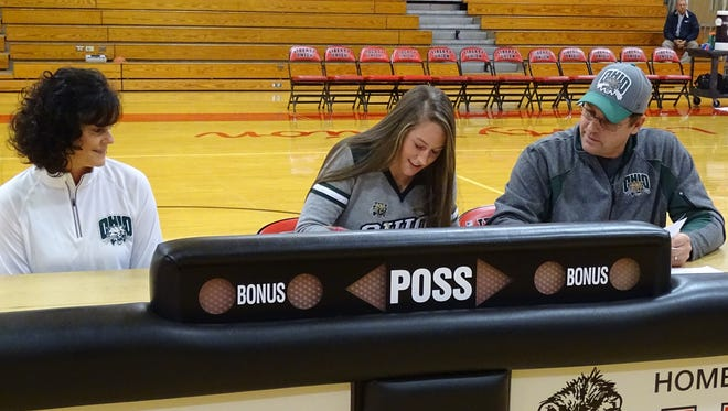Liberty Union senior Gabby Burris signs her national letter of intent to play basketball at Ohio University Wednesday as her parents, Molly and Kevin, look on.