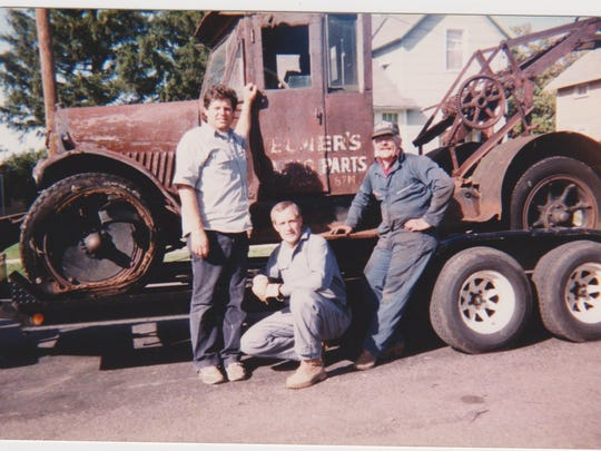 Jim Guck Sr., left, stands with two customers from Ohio who were purchasing an old Elmer's Tow Truck from Guck in this circa early 1980s photo.